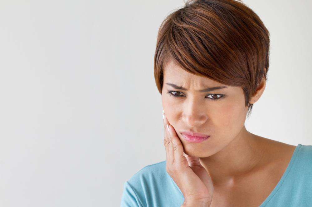 Woman holding her face in pain from tooth sensitivity near 27103