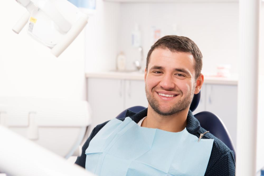 Patient smiling in treatment chair for dental exam & cleaning in Winston-Salem